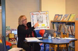 Garrison School Principal Stephanie Impellittiere shows off the newly arrived Philipstownopoly board game, a fundraiser by the Garrison and Haldane PTAs, at the Board of Education meeting Dec. 12.Photo by J. Tao