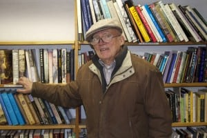 Frank Volkmann stands before his soon-to-disappear bookshelves. Photo by K.E. Foley