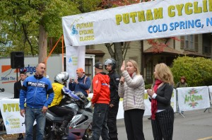 John Eustice of Sparta Cycling Inc., left, listens as Putnam County Director of Tourism Libby Pataki speaks to cyclists at the starting line on Main Street in Cold Spring on Oct. 14.Photo by J. Tao