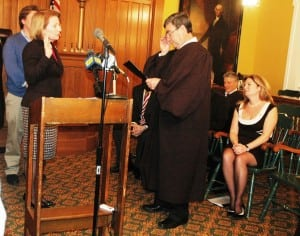 Barbara Scuccimarra takes her oath of office, surrounded by family and officials, including County Executive MaryEllen Odell, lower right. Photo by L.S. Armstrong