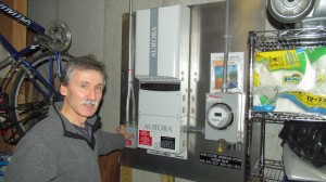Peter Henderson points to the inverter, which converts direct current generated by rooftop solar panels into alternating current that can be used in his home. Photo by M. Turton