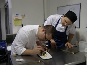 Swift Chef Brandon Collins, left, with evening garde manger Steven Hejnas, artfully creates a new menu addition.