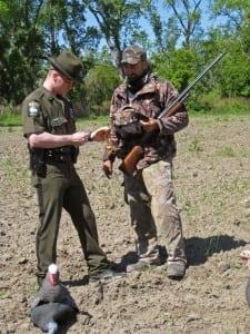 An ECO checks a turkey hunter's license.