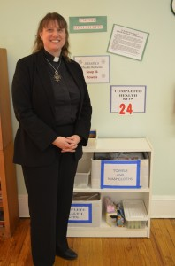 Rev. Margaret Laemmel by the health-kit station in the hall of the United Methodist Church of Cold Spring