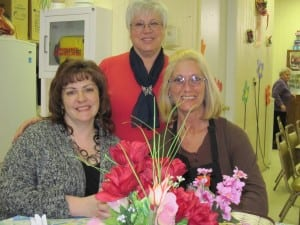 Site Manager Rhonda Haussman, left, transportation driver Maria Covelli, and Lorie Etta of food services