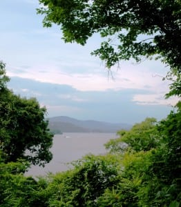 As twilight approaches, trees frame a view of the Hudson River at Mystery Point.
