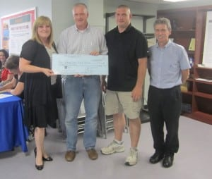 Dan Hughes, president of the Haldane Blue Devil Booster Club, presents a check to board members, left to right, Gillian Thorpe, Jon Champlin and Peter Henderson. Photo by A. Rooney