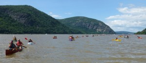 Two Row paddlers arriving in Cold Spring, with Storm King Mountain in the background. Photo by Andrew Courtney