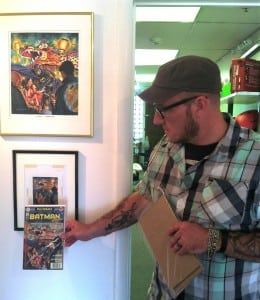 Taste Like Chicken and Short Walls Gallery owner Matt Held holds up Batman 'zine cover to artist Joel F. Naprstek's original watercolor sketch and final acrylic painting. Photo by Sommer Hixson