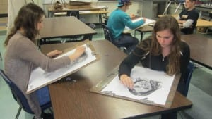 Students Kelly Vahos, left, and Shauna Ricketts are engrossed in working on their drawings of each other.
