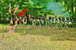 Members of the 5th NY Regiment of re-enactors fire a volley in salute over the graves of Revolutionary War soldiers at the Fishkill Supply Depot.