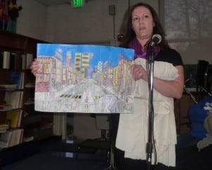 During a plea to the board to maintain the program, Haldane parent Cindy Chiera displays artwork her son made at school.