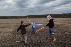 Raymond Hubbard plays with Star Wars light sabers with his sons Brady and Riley.