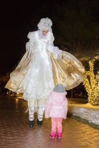 The Snow Queen Stilt Walker enchants a tiny visitor at Boscobel's 2013 Sparkle.