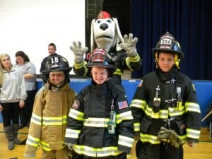 From left, Mairead O'Hara, Matthew Junjulas, and Will Etta suit up in firefighting gear.