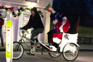 Santa arrives for tree-lighting celebration driven by John Miles of People's Bicycle.