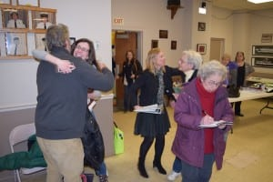 Dave Merandy gets a hug fron his wife Stephanie Hawkins while Marie Early (right) pours over the numbers one more time and Fran Murphy, second from right, receives congratulations.