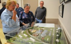 Attendees at the public hearing on the Butterfield redevelopment design study a model of the proposed complex.