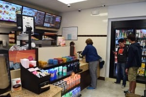 Customers line up inside Dunkin' Donuts. The former service station now also houses a convenience store.