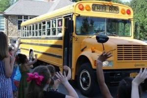 Theschoolbuscarryingthetwohonoreesmakesitsfirstcircuit,tothecheersofthekids.