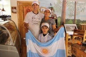 RinconArgentino'sproprietors,MarcoandRamonaAntonio,withtheirsonIvan,holdingupanArgentinianflagattheirnewcafé.