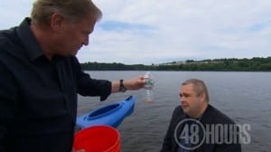 Peter Van Sant, with Michael Archer, holds a bottle with the amount of water drained from the kayak's drain plug opening (48 Hours)