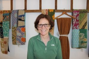 Hudson Natural's Marnie Henricksson, pictured in front of some of the textiles the store features. (Photo by A. Rooney)