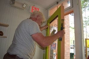 Hugh Moss replaces the broken window in the entrance door at Go Go Pops. (Photo by M. Turton)