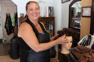 "TwistofFate'sSharonVerardore-workingher""model's""hairinpreparationforthereallook,tobeshownattheHairdressers'Ball.(PhotobyA.Rooney)"