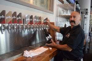 Bartender Ed Goldberg serves up a growler at Peekskill Brewery. (Photo by M. Turton)