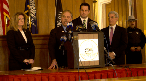 Dennis Sant at a press conference in January 2013. Behind him, left to right are County Executive MaryEllen Odell, then-State Sen. Greg Ball and Assemblyman Steve Katz (file photo by Kevin E. Foley)