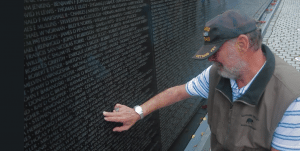 Mike Mastrolia rubs the name of Roy Parson of Perkins, Oklahoma, who died with 10 other soldiers in a helicopter crash in Vietnam in 1968. (Photo by Greg Gunder)