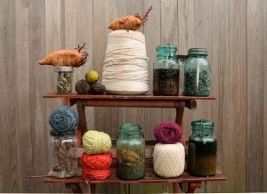 An assemblage of much that goes into Colorant: natural dyes, dye-containing shells and colored yarns (photo provided)