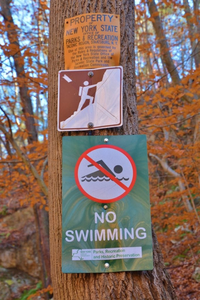 The New York State park system forbids swimming and climbing rocks at Indian Brook Falls, but the sign prohibiting rock-climbing no longer bears the red diagonal slash indicating a ban. (Photo by L.S. Armstrong)