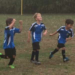 The Philipstown U8 Boys Storm enjoys its first team goal scored by Parker Larsen (middle). Oliver Sanders (left) and Kyoshi Tomasawa (right) help Larsen celebrate in the Oct. 30 against Newburgh. (photo provided)