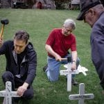 Father Shane Scott-Hamblen of St. Mary's-in-the-Highlands, Jack Dickerhof and Chip Kniffen place wooden crosses on the lawn of the church in preparation for Memorial Day. The work, which began May 22, is completed over several days. (Photo by Anita Peltonen)