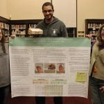 From left, Sabrina Ortquist, Bryan Ortquist and Julie Corbett, displaying the project description Corbett brought with her to the hand therapists' conference. (Photo by A. Rooney)