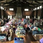 Tables piled with secondhand clothing at a past Ree Play sale (Photo provided)