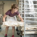 Erin Detrick loads loaves onto a rack for overnight proofing before being baked the next day. (Photo by Kevin Googan)