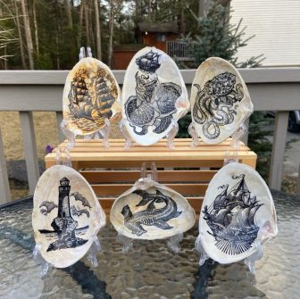 Ink illustrations on seashells, meant to resemble scrimshaw