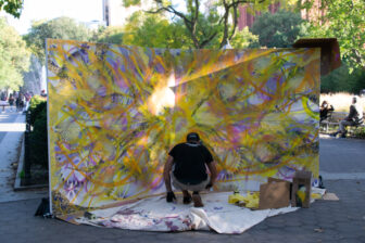 "Loray spray painting a layer of ""The Art of Dreaming"""