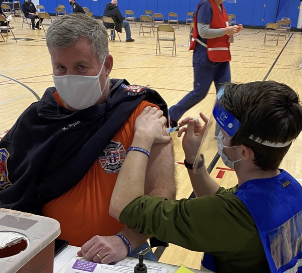 Keith Ryan, a volunteer firefighter, receives a vaccine